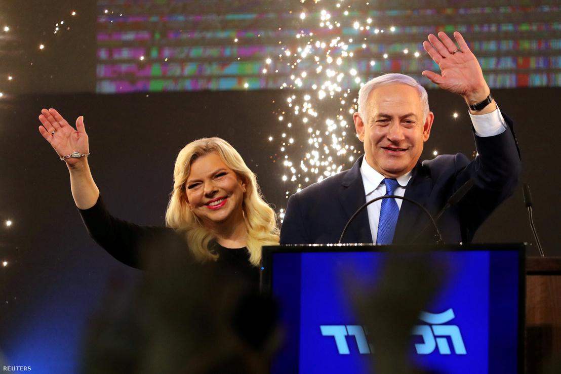 Benjámin Netanjahu és felesége, Sara integetnek az előzetes szavazat számlálások után a Likud párt székházában Tel Avivban 2019. április 10-én