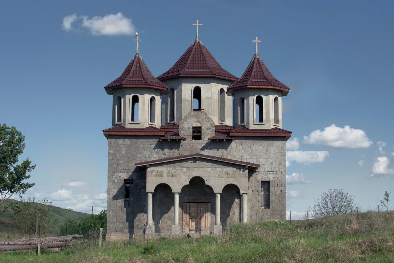 A templomok közül rengeteg egy kaptafára készül, a moldvai részen a fotós legalább 50 ugyanolyat látott. A forma azonos, esetleg a méretek változnak. Néhány építészeti motívum a családi házakra is átkerül. Erdélyben is rengeteg templom épül, ott még inkább érezhető a szimbolikus területfoglalás.                         Akár egy családi háznak is elmenne ez a Kolozs megyei, építés alatt álló templom.