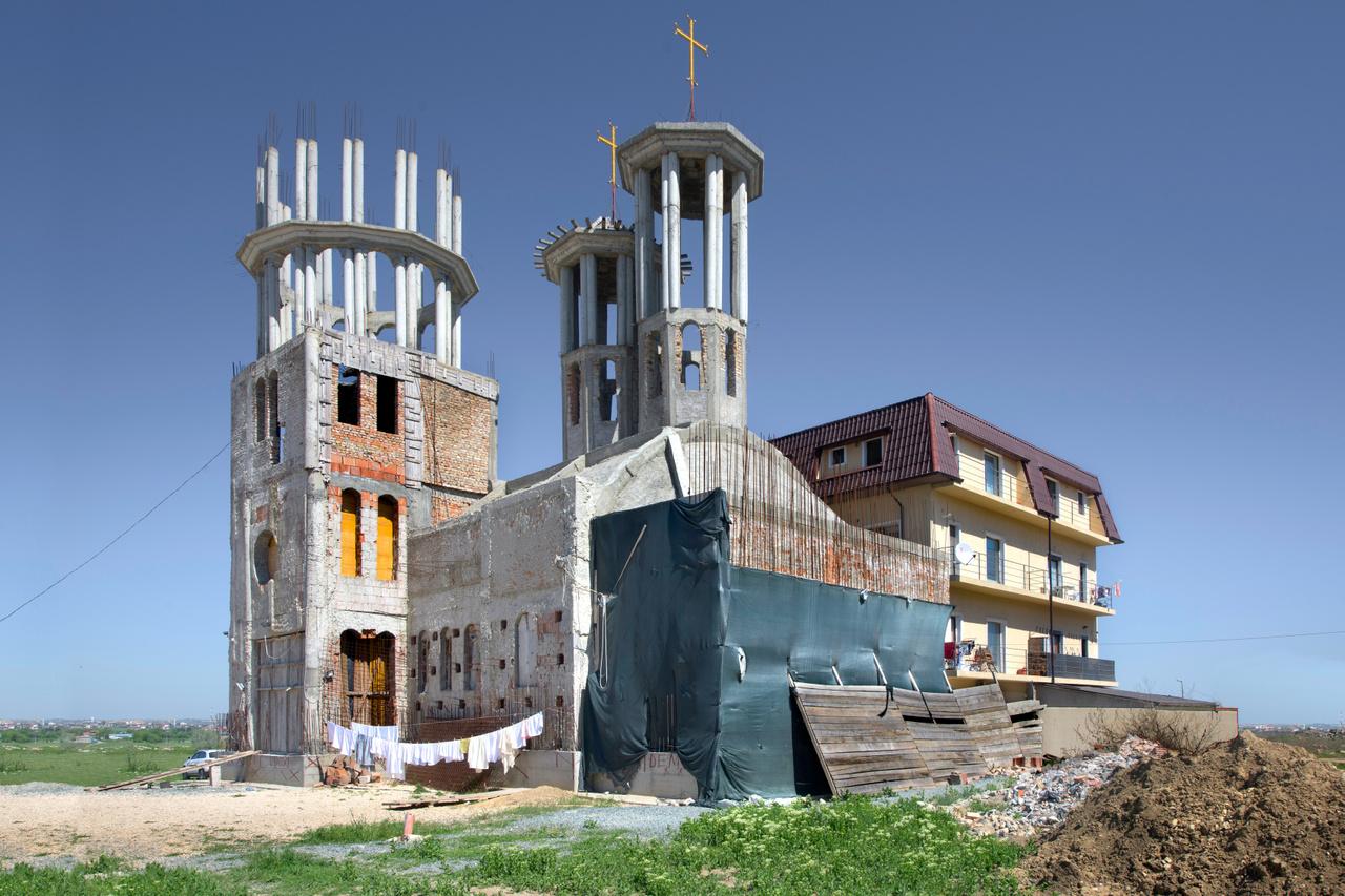 Az erőltetett templomépítés társadalmi feszültségeket is szül. Az ortodox egyház jórészt állami támogatásból építkezik, a projekt 70-80 százalékát tehát adókból teremtik elő, nem véletlen, hogy sokan pénzszórást, értelmetlen költekezést látnak a templomépítésekben. Az ortodoxok ráadásul más felekezetek elől is elszívják a levegőt, az egyházi támogatás közel 90 százalékát viszik el. A maradékon 16 másik felekezet osztozik. Érthetően a magyar közösségek szemét is szúrja az ortodoxosítás, náluk nem sok hagyománya van ennek a vallásnak, és ahogy a nyárádtői templomnál is láttuk, régi emlékek is elpusztulnak közben.                         Építés alatt álló templom Konstanca megyéből.