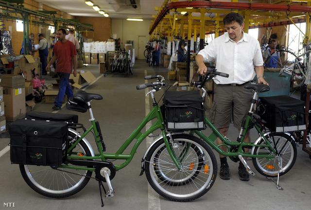 Neuzer András, az esztergomi székhelyű Neuzer Kerékpár Kft. tulajdonosa az általa tervezett 26 és 20 coll kerékátmérőjű postáskerékpárokkal a cég esztergomi üzemében 2009. július 14-én.