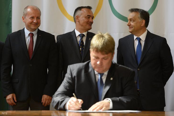 Orbán Viktor miniszterelnök (j), Simicskó István, az Emberi Erőforrások Minisztériumának sportért felelős államtitkára (b) és Borkai Zsolt, a Magyar Olimpiai Bizottság elnöke beszélget, miközben Szűcs Lajos, a Magyar Tenisz Szövetség elnöke aláírja a kormánnyal kötött megállapodást a Parlamentben 2013. július 9-én