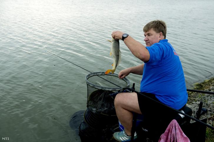 Szűcs Lajos fideszes országgyűlési képviselő, a Mohosz elnöke a kifogott halat mutatja a Matyi-éri víztározónál, Szeged közelében 2018. június 7-én.