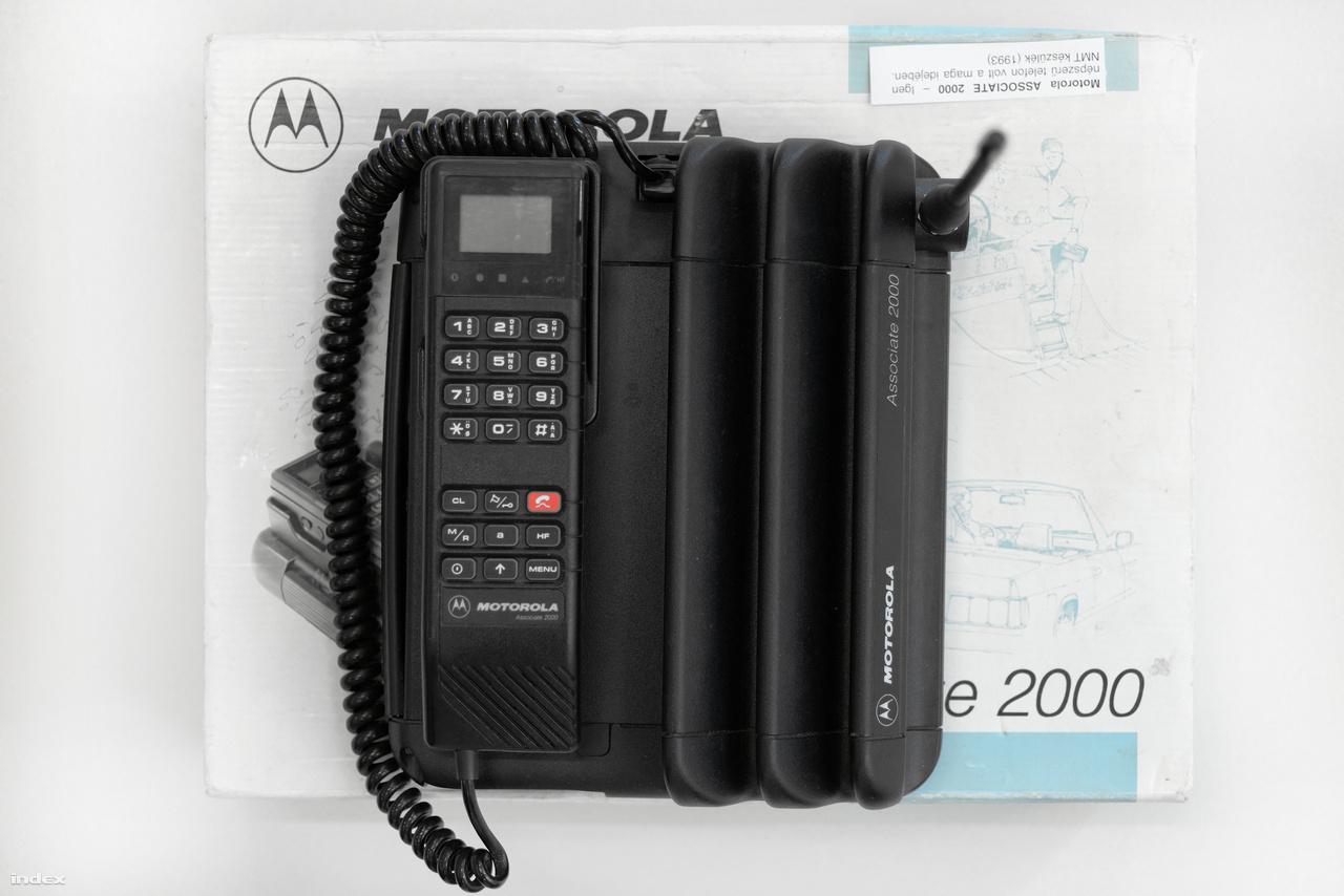 """Motorola Associate 2000 """"főnöktelefon"""" 1993-ból. (""""Én először akkor láttam ilyet, amikor 2004 nyarán diákmunkában öltözősként dolgoztam Debrecenben a kerekestelepi strandon, és egy ötven év körüli, barnára sült, napszemüveges, albán maffiózónak kinéző fickó ilyennel slattyogott be vietnámi papucsban, és leadta cuccaival együtt, lelkemre kötve, hogy két szemem legyen rajta"""" – Nagy Attila Károly.)"""