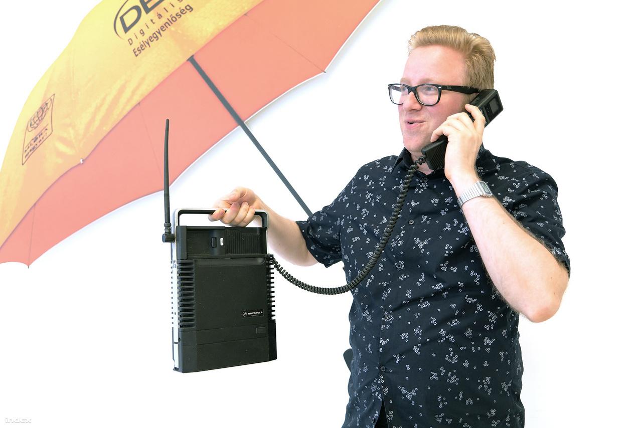 Képes Gábor, a kiállítás egyik rendezője és egy Motorola MCR 4800XL. Egy ilyen táskányi méretű, még analóg technológiát használó                         készülékről indította az első magyarországi mobilhívást Bod Péter Ákos, akkori ipari és                         kereskedelmi miniszter 1990. október 15-én.