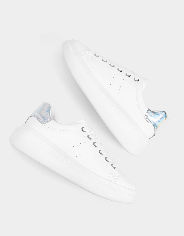 A sima, fehér sportcipőt még nőiesebbé és divatosabbá tehetik az apró, színváltós, hologramos hatású díszítések. Ez a darab a Bershkában 8995 forint.