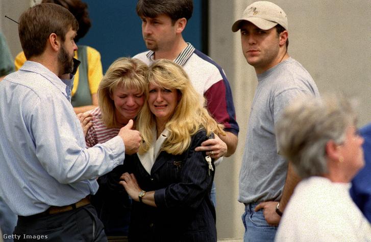 Az egyik bent rekedt diák édesapja Bill Curry tájékoztatja a családot, hogy a lányuk Kendra, és unokahúga Kami elbarikádozta magát a Columbine iskolai vécében, miközben a két fegyveres még bent lövöldözik. Középen az édesanya és a nagynéni látható 1999. április 20-án