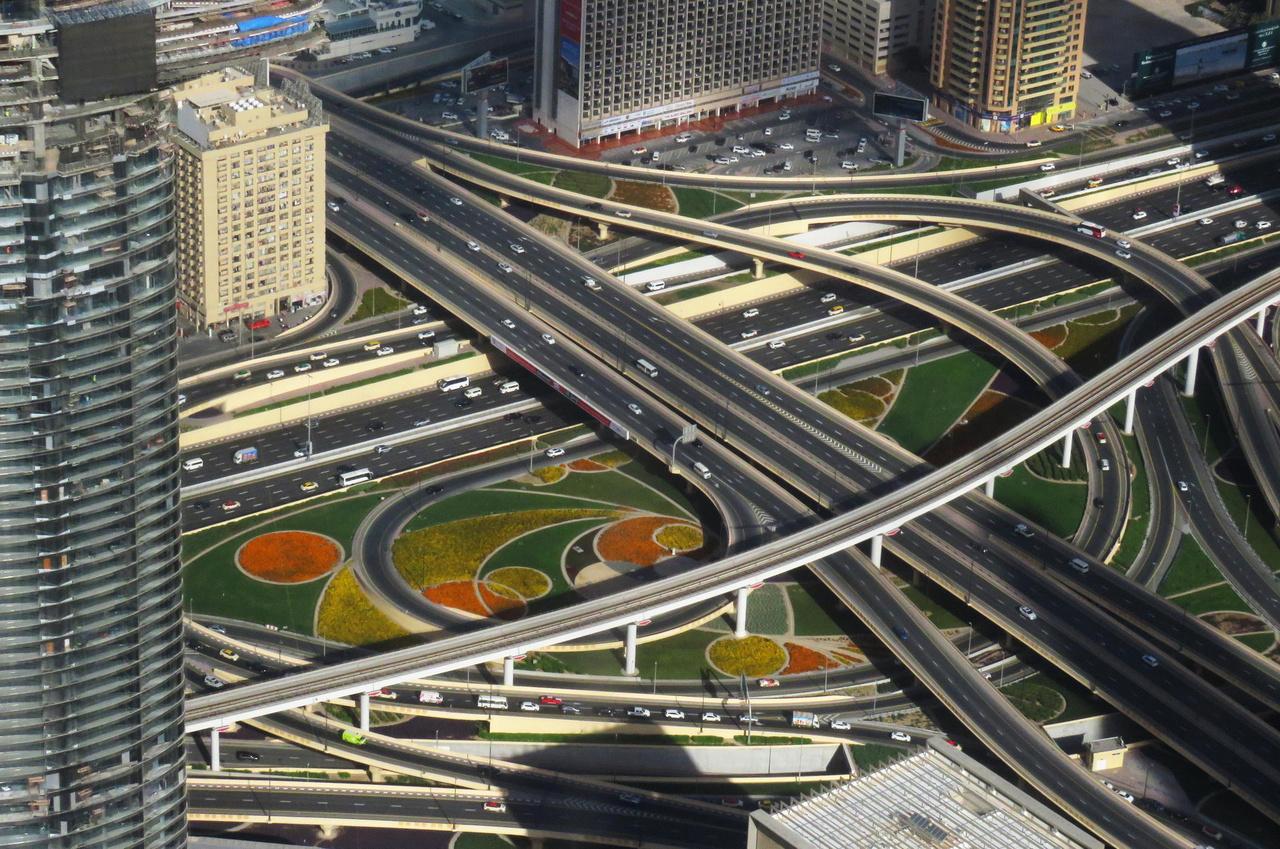 Forgalmi csomópont virágos parkkal a Burdzs Kalifa 125. emeletéről fotózva. A toronyház jelenleg a Föld legmagasabb épülete, 6 év alatt építették fel 1,5 milliárd dollárból. Az olaj már csak Dubaj bevételeinek 6 százalékát adja (most épp egy nagy naperőművet építenek), ezért a bevételeket a turizmusból igyekszenek növelni. Ehhez viszont vonzó, látványos beruházások szükségesek.