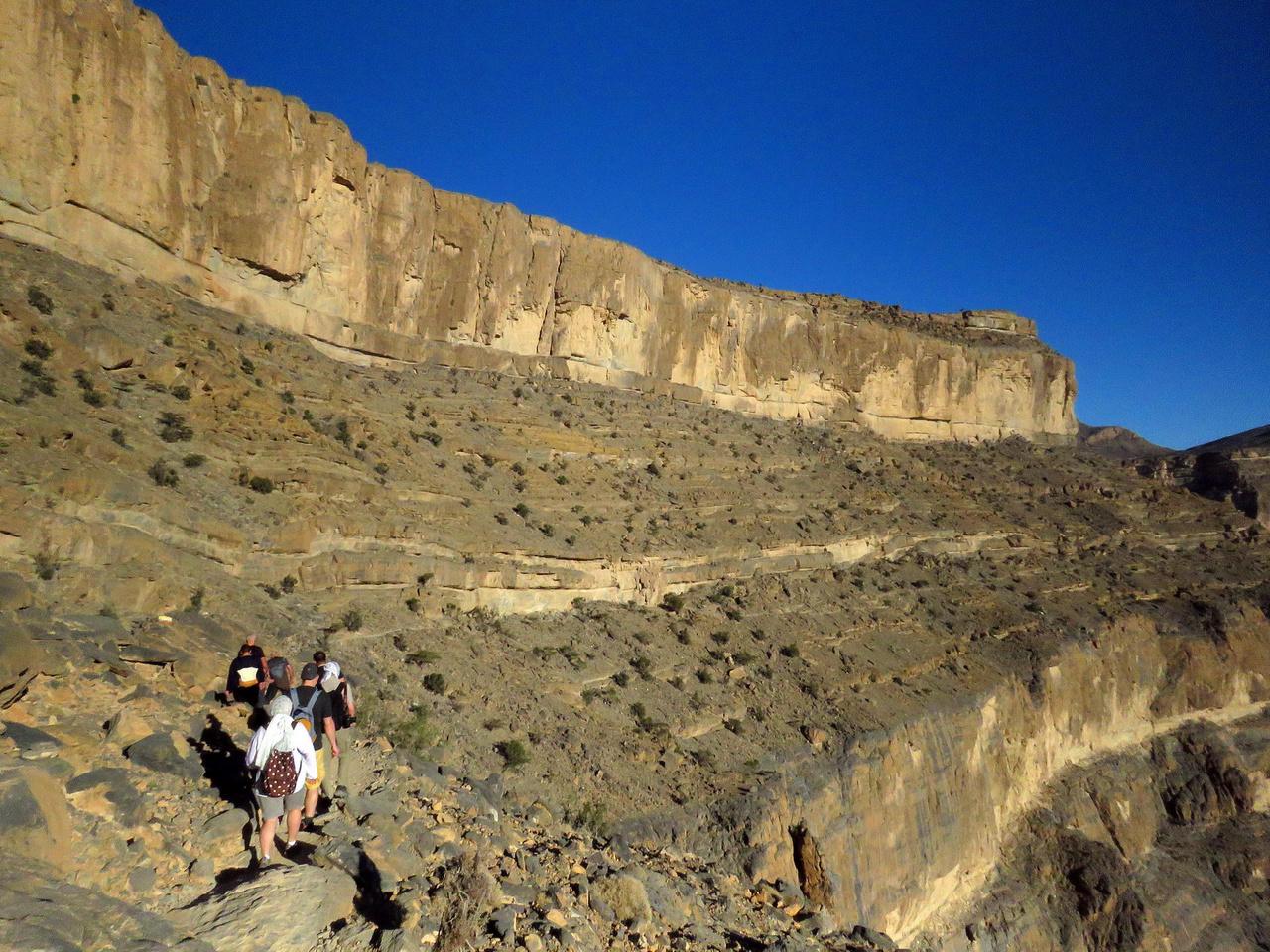 Gyalogtúrán a Gul vádi oldalában. A Wadi Gult Arábia Grand Canyonjaként is emlegetik, és a hasonlítás egyáltalán nem alaptalan. A kanyon falainak magassága eléri az 1500 métert, a kilátás lélegzetelállító. A völgy felső végében régen egy kis falucska, As-Sab működött, zord körülmények között, de sikeresen. Volt elég vizük, a teraszokon zöldséget és gyümölcsöt termeltek, kecskéket tartottak. A nehézségek ellenére is biztonságosabb volt az élet a rejtekhelyen, mint a sűrűbben lakott vidékeken, ahol rendszeres voltak a rablótámadások.