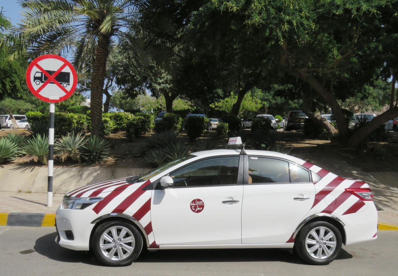 Maszkati taxi, figyelemfelhívó csíkozással. A főváros hosszan elnyúlik a tengerparton, ezért a nem túl drága taxik a turistáknak is sokat segítenek abban, hogy az egymástól távoli látnivalókat kényelmesen elérjék.