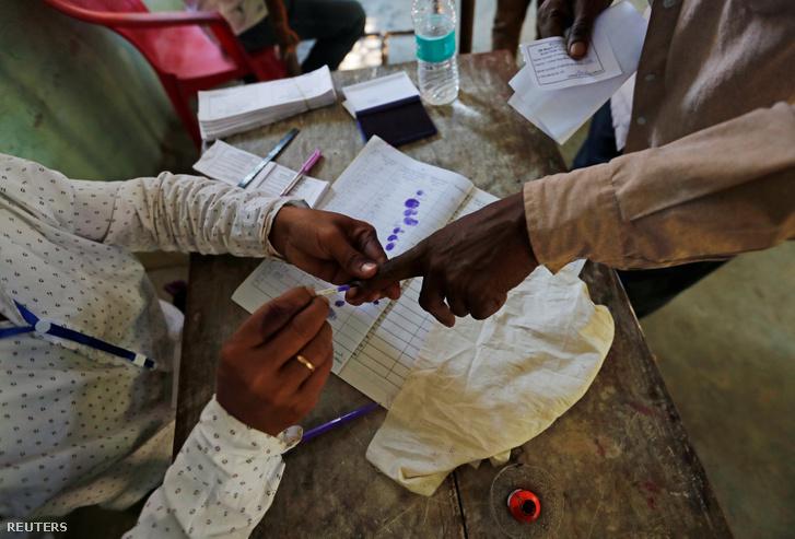 Tintával jelölik meg egy férfi ujját, miután leadta a szavazatát Majuliban