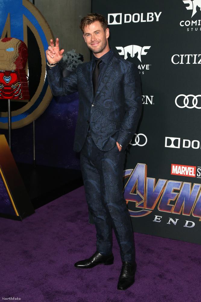 Az immár rövid hajú Chris Hemsworth egy sötétkék, mintás öltönyben integetett