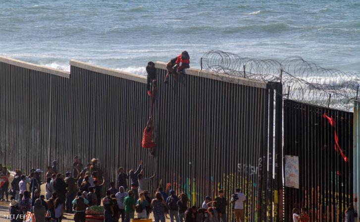 Menekültek próbálnak átjutni a mexikói-amerikai határkerítésen a Baja California mexikói állambeli Tijuana tengerpartján 2019. március 19-én.