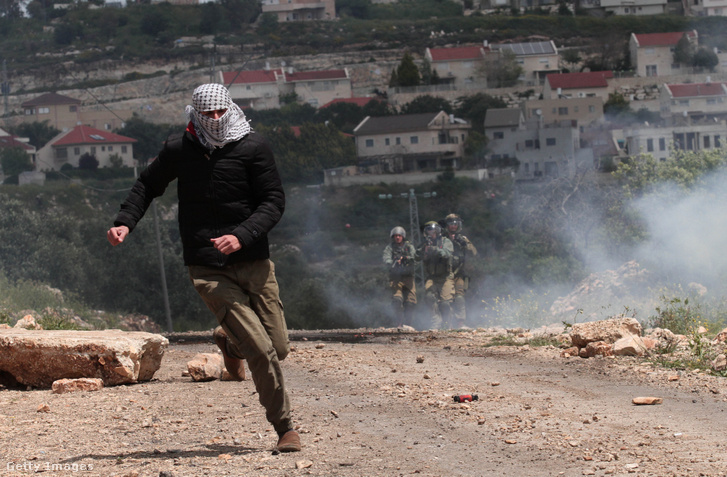 Palesztin tüntető fut el az izraeli hadsereg katonái elől ciszjordániai Kafr Qaddum falu közelében 2019. április 19-én