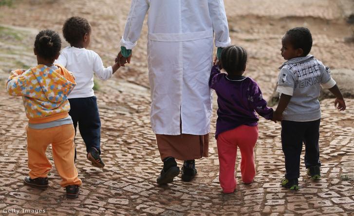 Nő sétál gyerekekkel az etiópiai árvaház és kórházi képzési központban 2013. március 19-én.