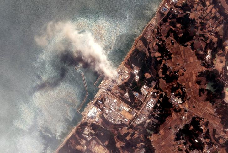 Műholdkép a füstölgő fukusimai erőműről a földrengést és szökőárt követően 2011. március 14-én. A japán hatóságok szerint a felszálló füst radioaktív anyagot juttatott a levegőbe.