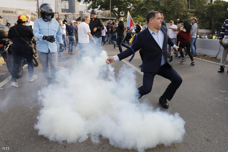 Juan Guaidó venezuelai parlamenti elnök, ellenzéki vezető egyik támogatója visszadobja a katonák által feléjük kilőtt egyik könnygázgránátot a caracasi Carlota légi támaszpontnál tartott kormányellenes tüntetésen 2019. április 30-án.