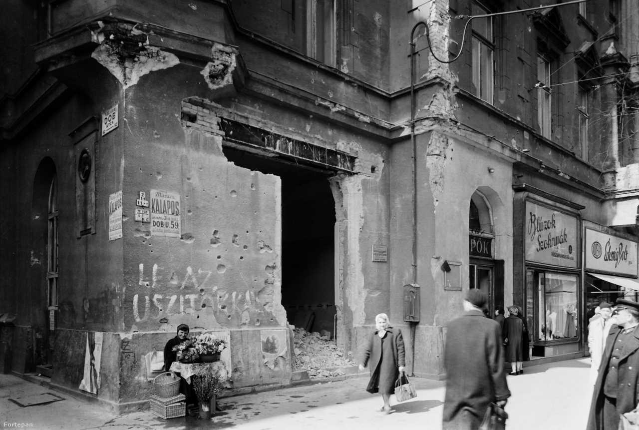 """A Dob utca és az Erzsébet (majd Lenin) körút sarka 1948-ban és 1957-benA háború után három évvel az egykori Meteor kávéház előtt kendős asszony árul Világosságot és Magyarságot. Mögötte látszik még a szociáldemokrata párt kongresszusi plakátjából """"A béke és a jólét felé vezet""""-felirat vége, teljes takarásban a """"Ma a demokráciáért, holnap a szocializmusért!"""" Utolsó nyomai ezek a szocdemeknek, a párt 1948 nyarán Magyar Dolgozók Pártja néven egyesült Rákosi Mátyás kommunista pártjával. Aztán 1957-ben ugyanott. A találatot kapott bolthelyiség előtt, Marácz kalapos táblája, ötvenhatos golyónyomok, """"Le az uszítókkal""""-felirat alatt egy nő barkát árul. A forradalom utáni első tavaszon még nem dőlt el, hogy reform vagy megtorlás jön. Az élet mindenesetre megindult. Vagy csak folytatódott."""