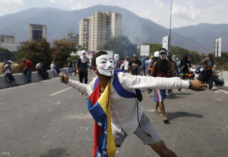 Rendőröket dobál egy álarcos tiltakozó a Nicolás Maduro venezuelai elnök elleni tüntetésen Caracasban 2019. május 1-jén.