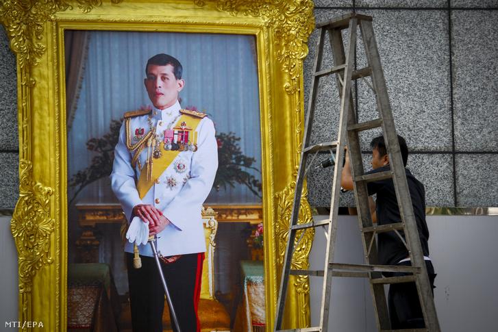 Munkások függesztik fel egy hivatali épület falára Maha Vadzsiralongkorn thai uralkodó aranyszegélyű képkeretben lévő óriásfényképét Bangkokban 2019. április 23-án.
