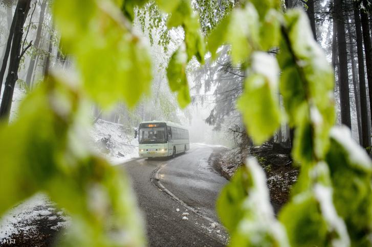 Autóbusz halad a behavazott Kékesen 2019. május 6-án.