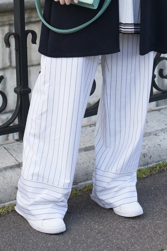 A hosszú, bő nadrág, ami a cipőt is takarja, nem engedi láttatni a láb vonalait. Szélesebbnek mutatja a bokát, lekerekített orrú cipővel pedig még erősebb a vastagító hatása.