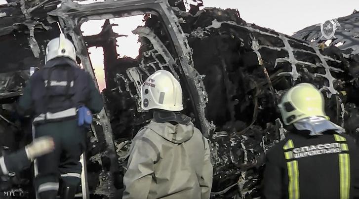 Az orosz Nyomozó Bizottság által közreadott, videofelvételről készített képen a bizottság munkatársai a kiégett roncsnál dolgoznak a moszkvai Seremetyevói repülőtéren 2019. május 6-án