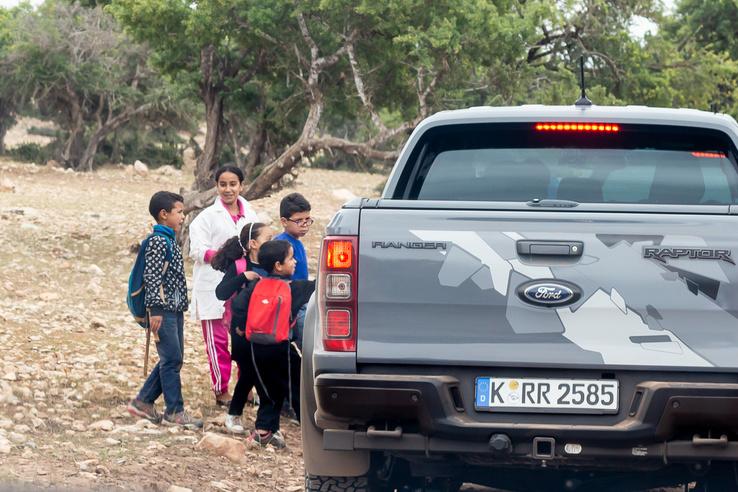Nagyon Afrika: gyerekek csodálkoznak rá az új pickupokra. A háttérben zöldellnek az argánfák