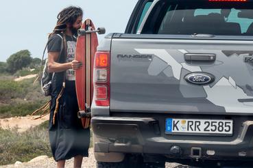 Bestoppolt a konvojba egy helyi raszta. A srác turistáknak árul karkötőket Szavírában és ehhez húsz kilométert longboardozik oda-vissza az üres utakon