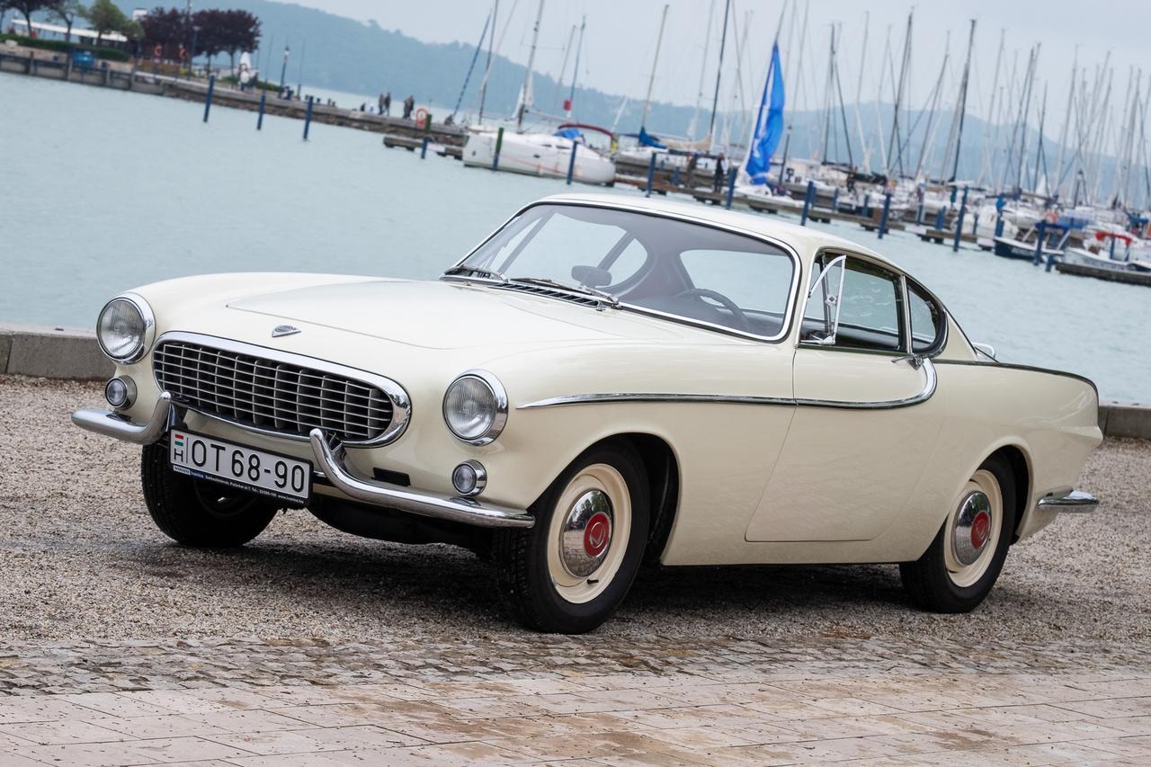 Simon Templar Füreden járt? Az lehetetlen, mert az őt megszemélyesítő színész, Roger Moore sajnos már a felhők fölött terelgeti a saját Volvo P1800-asát. Ez a földi és nagyon is kézzel tapintható, '63-as példány nem csak azért érdekes, mert elképesztően szépen megmaradt, hanem mert egyike a legkorábbi, de már svéd gyártású példányoknak (a legelsők Angliában, a Jensennél készültek), még kicsi dísztárcsákkal, elkanyarított oldaldíszléccel és ökörszarv-lökhárítókkal