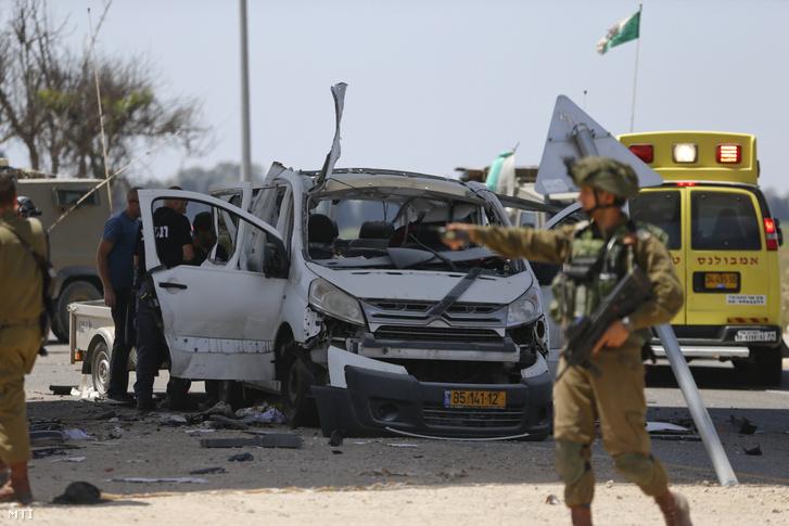 Egy Gázai övezetből kilőtt rakéta által eltalált autó előtt egy izraeli katona a Gázai övezet határának közelében 2019. május 5-én.