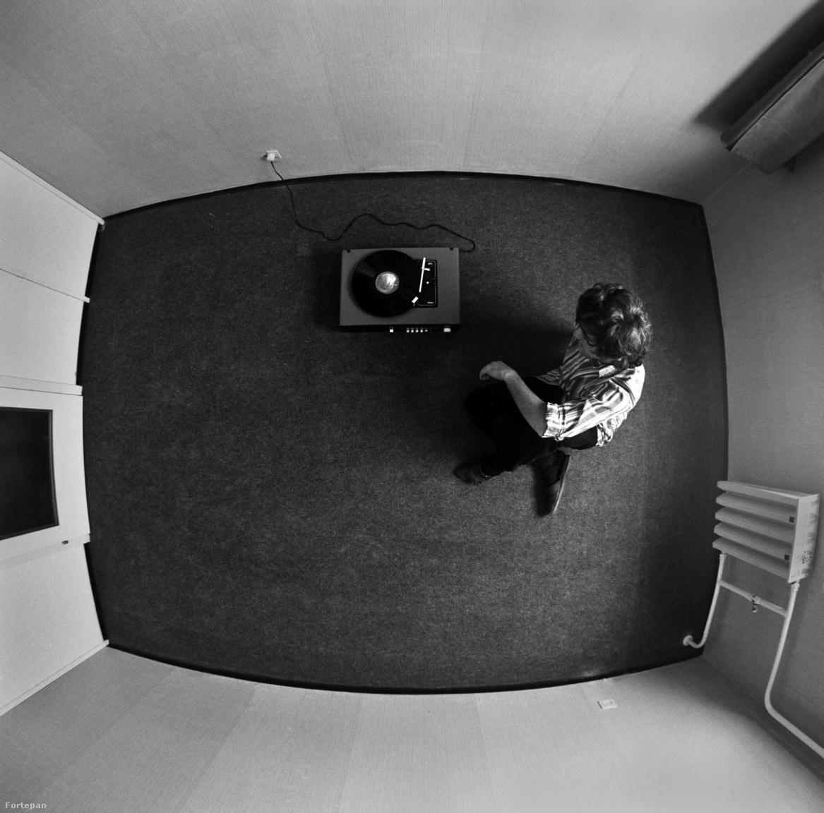 Ez a kép Horváth Péter talán kedvenc képe a sorozatból. Sokan kérdezik tőle, hogy milyen trükkel csinálta a képet, de nekünk elmesélte a bűvésztrükköt: egyszerűen a csillárnak kirakott kampóra akasztotta a fényképezőgépét, beállította időzítőre és kiszaladt a szobából, ahol egy barátja és a lakás első és legfontosabb tárgya, egy lemezjátszó látható.