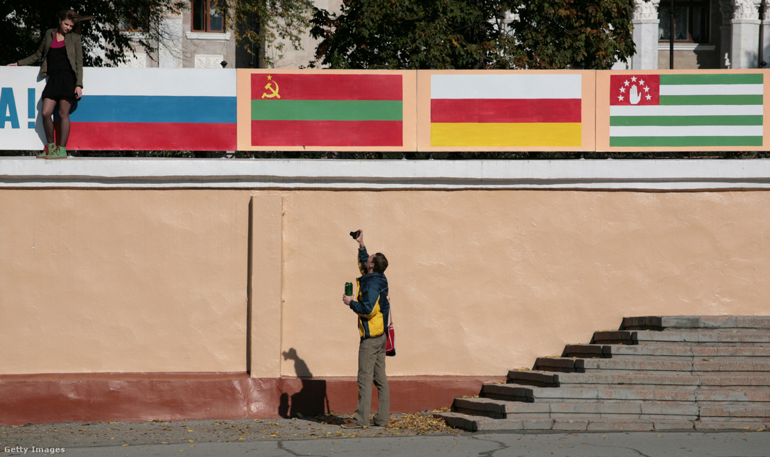 Egy férfi fényképezi a barátnőjét Oroszország, Dél-Oszétia és Abházia zászlaja előtt Tiraspolban Moldovában, Transnistria régióban 2008. október 19-én.