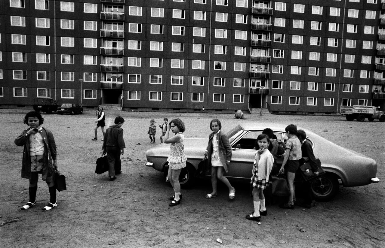 Egy egészen különleges autó a telepen. A fiúk a járgányt, míg a lányok a fotóst figyelik. Kezdetben amúgy nem volt sok autó a telepen, éppen ezért sok parkolót csak utólag alakítottak ki.