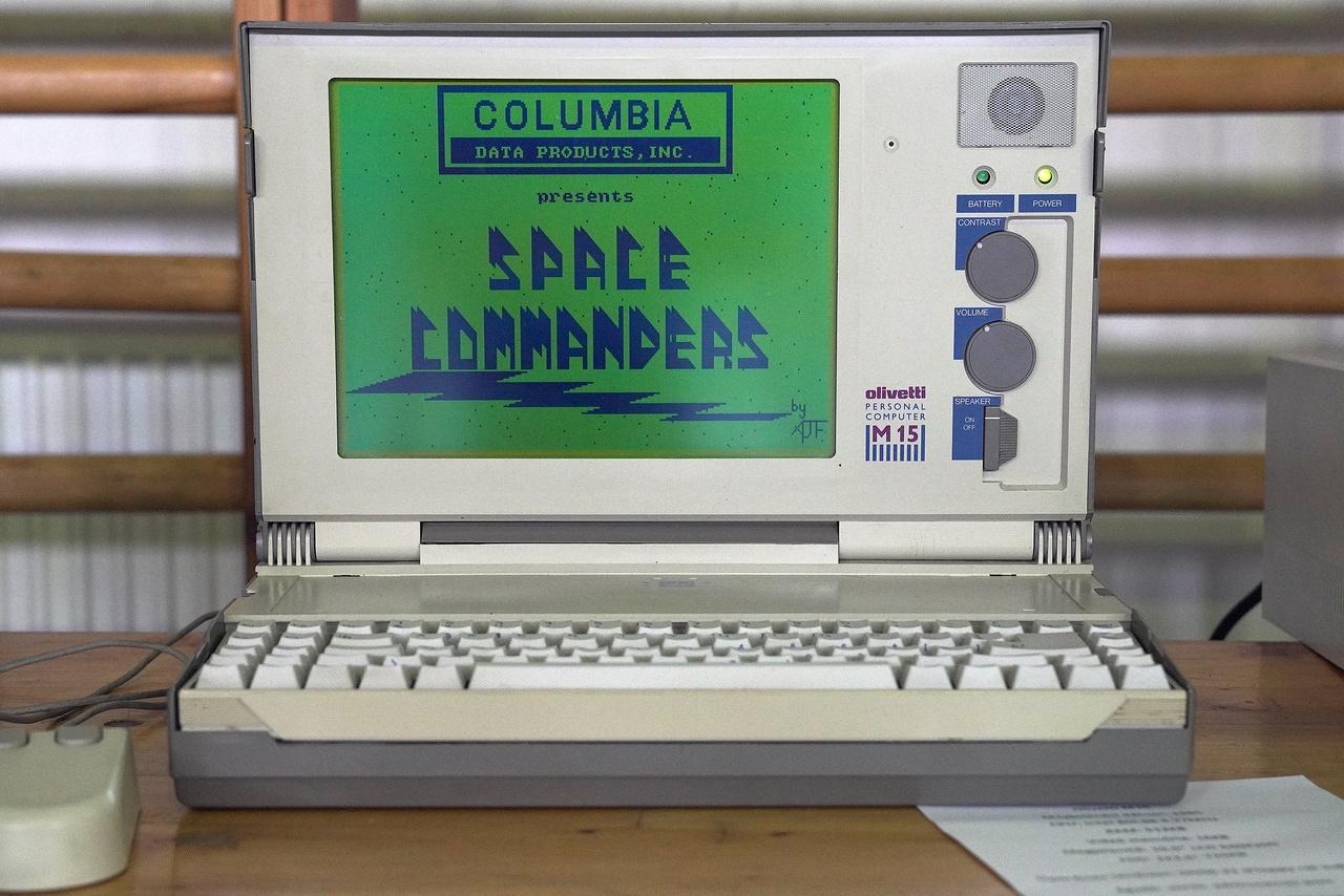Az egyik legszebb laptop a kiállításon, egy 1985-ös Olivetti M15. 4,77 MHz-es Intel 80C88 processzor ketyeg benne, 512 kB RAM, 16 kB videómemóriája van, DOS 6.22-es oprendszer fut rajta (floppyról indítva), a kijelzője pedig kétszínű 10,5 inches, 620*200 pixeles felbontású LCD. 1987-ben kétezer dollárba került egy ilyen. Csak úgy hasít rajta a Space Commanders.