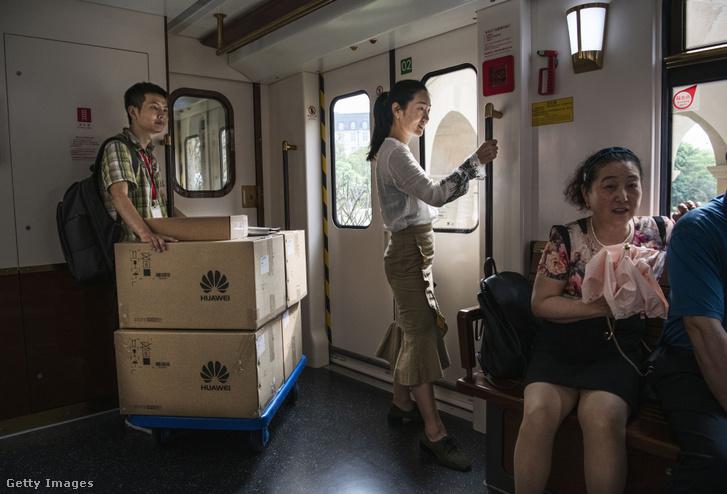 """Huawei dolgozó szállítja a csomagokat az alkalmazottak által használt vonaton """"Ox Horn"""" nevű fejlesztési kampuszon Dongguanban 2019. április 24-én"""