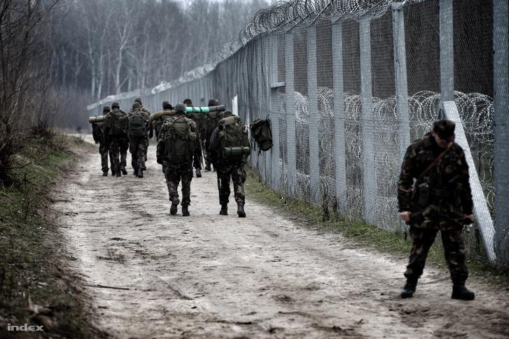 Katonák mennek Ássothalomnál a határt lezáró kerítés mentén 2016. február 9-én.