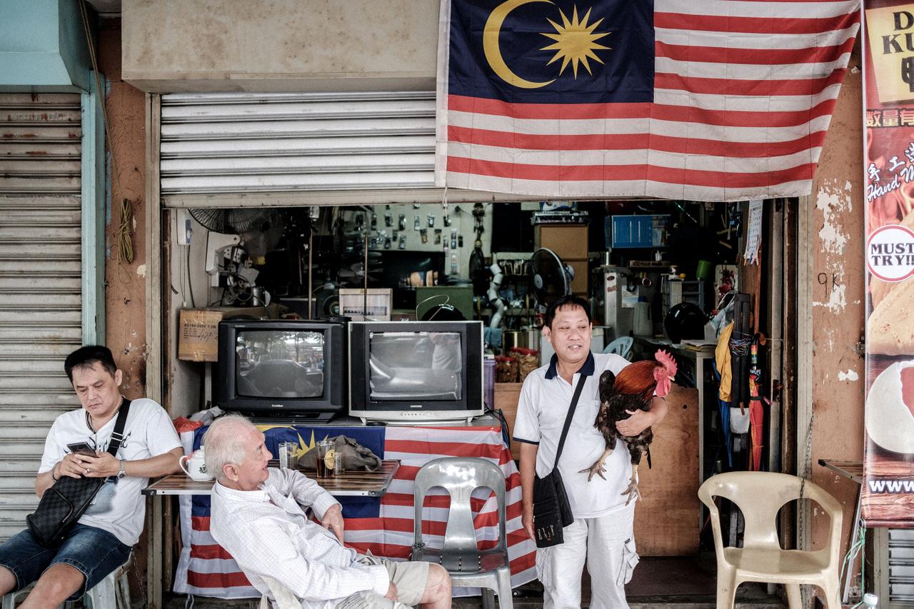 """Január 16.                         """"Utazásaim alatt a lehető legtöbb helyre gyalog próbálok eljutni, ez alatt az idő alatt ismerkedem a helyi viszonyokkal, a környezettel és a helyiekkel, ki tudja mibe fut az ember. Már nem is igazán tiszta, hogy miért kezdem el fényképezni a fickókat, talán a zászló vált ki belőlem valamit. Ők sem értik, mi lehet bennük olyan érdekes Kuala Lumpur egy olyan negyedében, ahol ritkán járnak turisták. Amikor a szélső arc kiszúrja a kakast a baseball sapkámon, heves mutogatás és nevetgélés közepette hátraszalad a műhelyszerű kifőzdéjébe, és előhozza Johnnyt, a kakast, hogy büszkén mutassa, neki is van."""""""