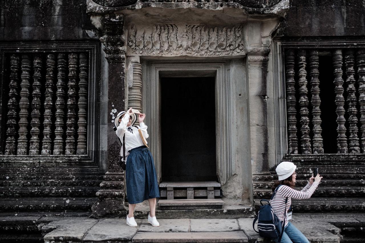 """Január 20.                         """"Ha az angol partituristák épp nem Belső-Erzsébetváros megmaradt kockaköveit koptatják Budapesten, akkor valószínűleg a kambodzsai Siem Reap valamelyik partihoszteljében próbálnak időben felkelni, hogy eljussanak Angkor ősi templomjainak egyikébe. Így nem kell álmos és másnapos angolok között cirkálnom a romok között reggel, arra viszont nem számítok, hogy a többezer kínai esernyő és szelfibot szinte mindent eltakar a látnivalókból. Szerencsére hamar ráeszmélek arra, hogy a romok között akad egy másik téma is, a minden előtt szelfiző és mindent megörökítő turista. Nem tudom, hogy azért, mert már nem fértek el Kambodzsában, de időközeben Kína megépítette a saját játszóterét, Angkor Wat tökéletes másolatát Nanningban."""""""