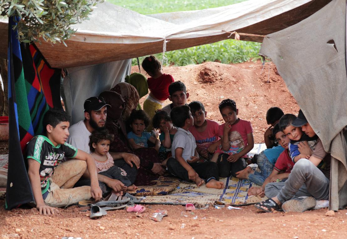 Lakóhelyüket elhagyni kényszerült szíriai család ül egy sátorban az Atmeh városhoz közeli olívaültetvényen, Idlib tartományban 2019. május 16-án
