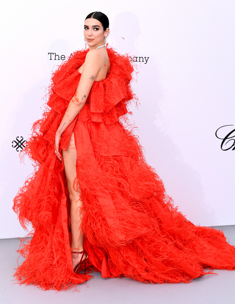 Dua Lipa egy teátrális piros ruhában jelent meg, ami annyira fel volt vágva oldalt, hogy el sem tudjuk képzelni, egyáltalán mi tartotta a textilt az énekesnőn