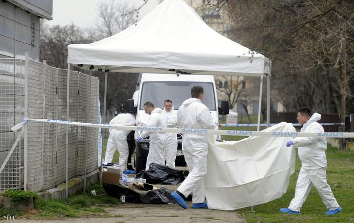 A rendőrség bűnügyi technikusai helyszínelnek egy letakart holtteste mellett