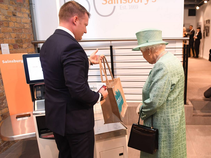 A Sansbury's alkalmazottja tanítja a királynőt, hogyan kell az önkiszolgálót használni.