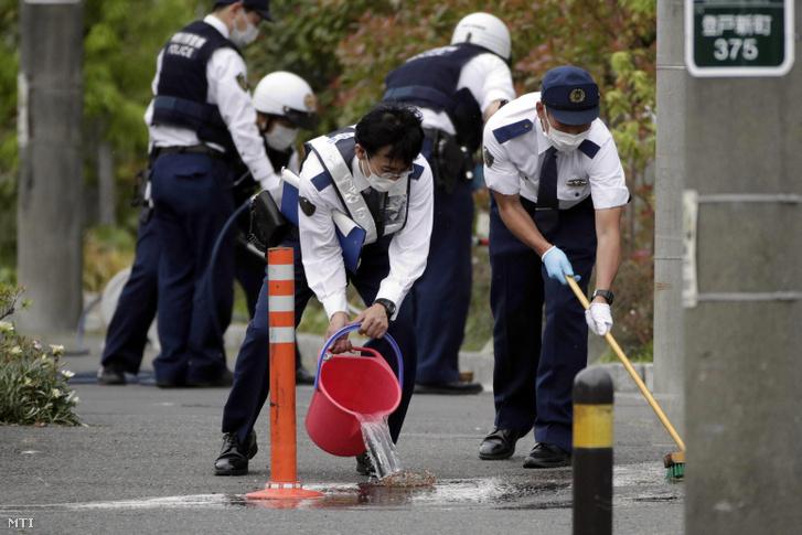 Rendőrök takarítják a Tokió környéki Kavaszakiban elkövetett késes támadás helyszínét 2019. május 28-án.