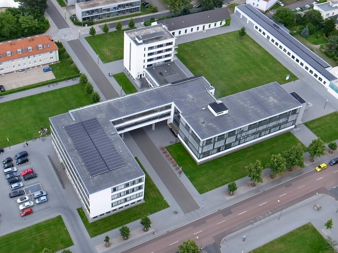 """A Bauhaus tömbje a levegőből - ahonnan a tervező Gropius szerint a legjobban néz ki a ház. Balra a """"csendes"""" szárny, szobákkal, tantermekkel, adminisztrációval. Onnan híd ível át a ma már sétálóvá alakított utca, a Bauhausstrasse felett, benne az igazgató szobája. A másik oldalon a lépcsőház, amihez jobbra """"alul"""" a zajos és fényigényes műhelyek, """"felfelé"""" az előadón és az étkezőn keresztül a kollégiumi tömb kapcsolódik."""