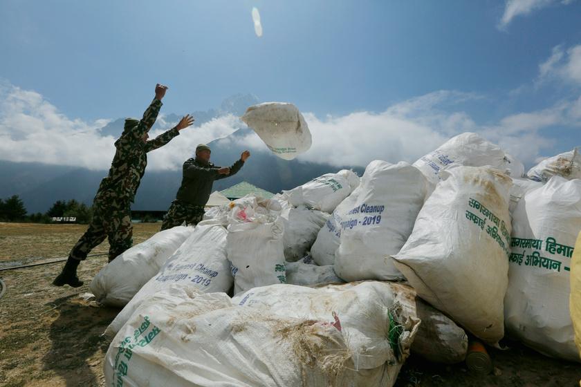 Katonák szeméttel teli zsákokat pakolnak a Mount Everest lábánál, Namche Bazar település közelében 2019. május 27-én.