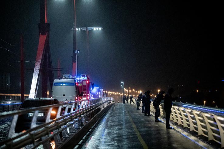 A Rákóczi hídon rendőrök és tűzoltók elemlámpákkal pásztázták a viharos folyót.