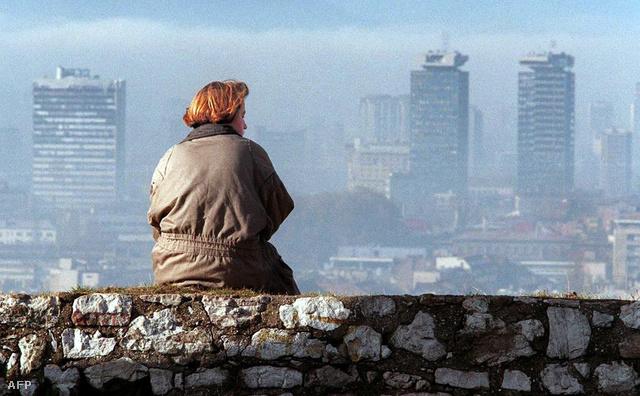Egy nő a lerombolt Szarajevó város felett, egy mesterlövészektől védett pontról figyeli otthonát.