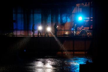 Rendőrök és tűzoltók a Kvassai zsilipnél elemlámpák fényénél vizsgálják végig a vízet és partot.