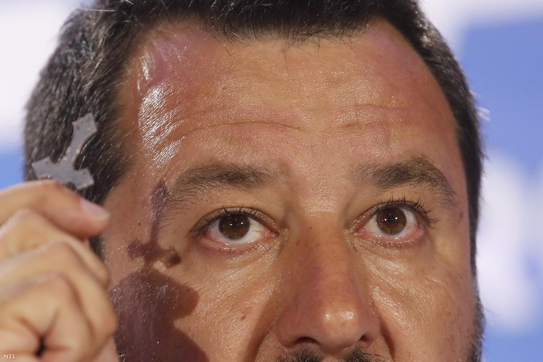 Matteo Salvini olasz miniszterelnök-helyettes és belügyminiszter, a Liga pártszövetség vezetője kezében kereszttel az európai parlamenti választások estéjén tartott sajtóértekezletén a párt milánói központjában 2019. május 26-án.