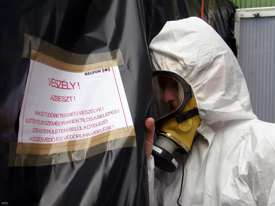 2005. május 11. Egy munkás védőfelszerelésben lép be az azbesztmentesítésre kijelölt területre az Ybl-díjas Rózsakerti lakótelep egyik épületében. Egy felmérés megállapította hogy a lakóépületek alagsoraiban rákkeltő hatású szórt azbeszt található.